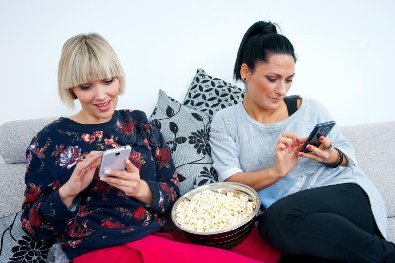 2 привлекательных друз женщины с мобильным телефоном и попкорном стоковое изображение rf