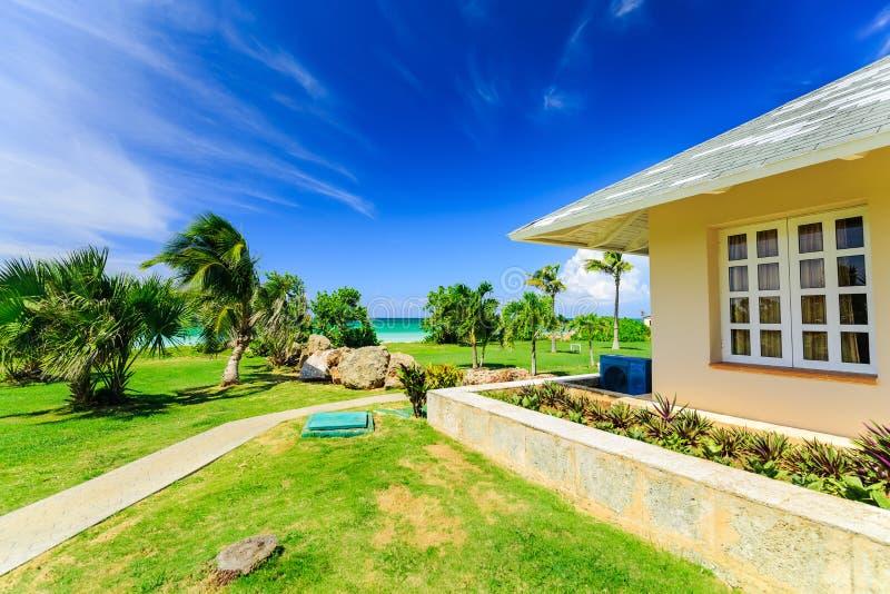 приглашая красивый естественный взгляд ландшафта дома виллы в тропическом праве сада около пляжа и спокойная бирюза смягчают oc стоковая фотография