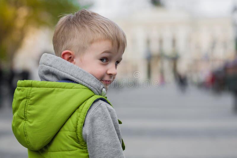 Приглашая любознательный маленький красивый мальчик смотря камеру стоковая фотография rf