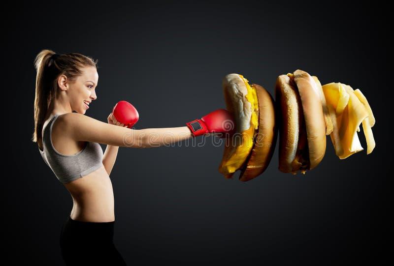 Пригонка, детеныш, напористая женщина кладя нездоровую еду в коробку стоковая фотография rf