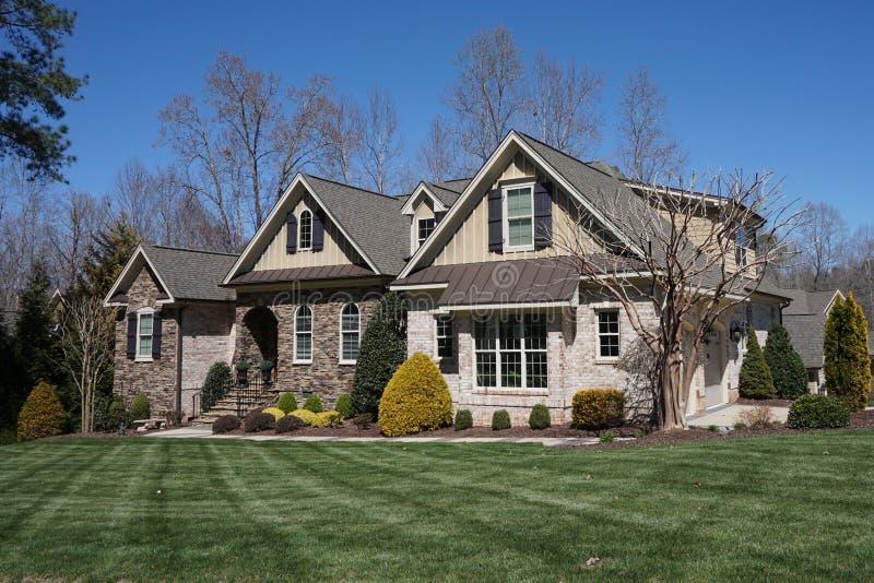 Пригородный дом с экстерьером камня и кирпича и славный благоустраивать в районе в Северной Каролине стоковые фотографии rf