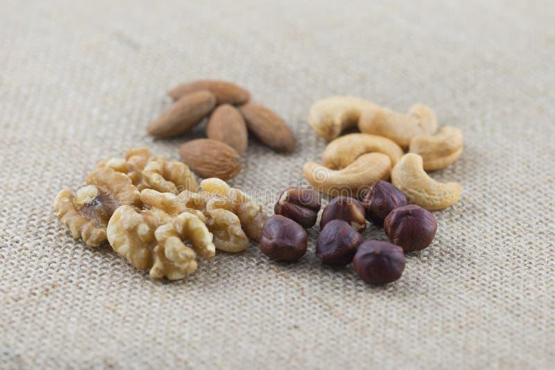 Пригорошня гаек анакардии, миндалин, грецких орехов и фундуков на ткани мешковины стоковое фото rf