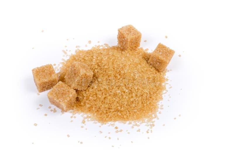 Пригорошня желтого сахарного песка и кубов желтого сахарного песка стоковые изображения