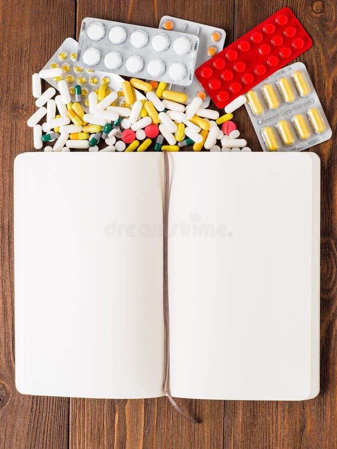 Пригорошня разбросанных медицин, пилюлек и таблеток и блокнота o стоковая фотография rf