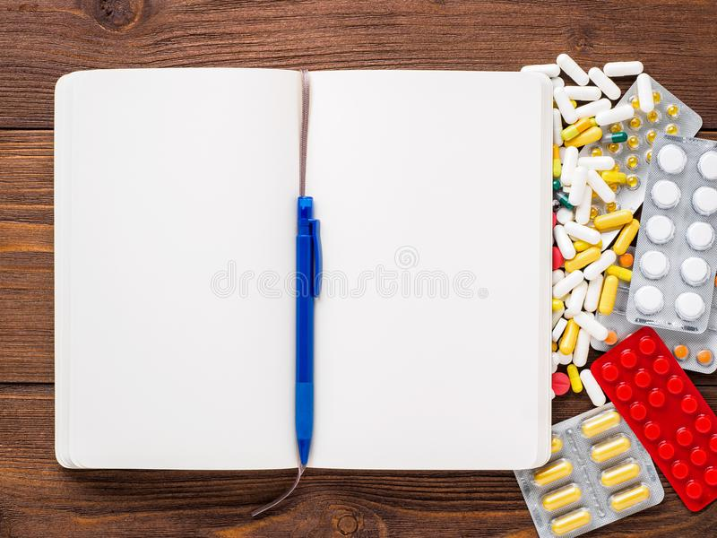 Пригорошня разбросанных медицин, пилюлек и таблеток и блокнота o стоковое изображение