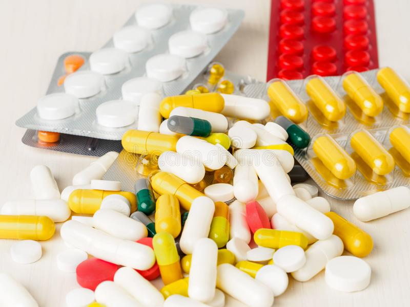 Пригорошня разбросанных медицин, пилюлек и таблеток на белом backg стоковое изображение