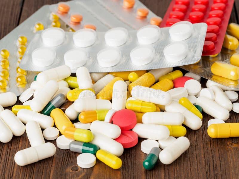 Пригорошня разбросанных медицин, пилюлек и таблеток на коричневом woode стоковая фотография