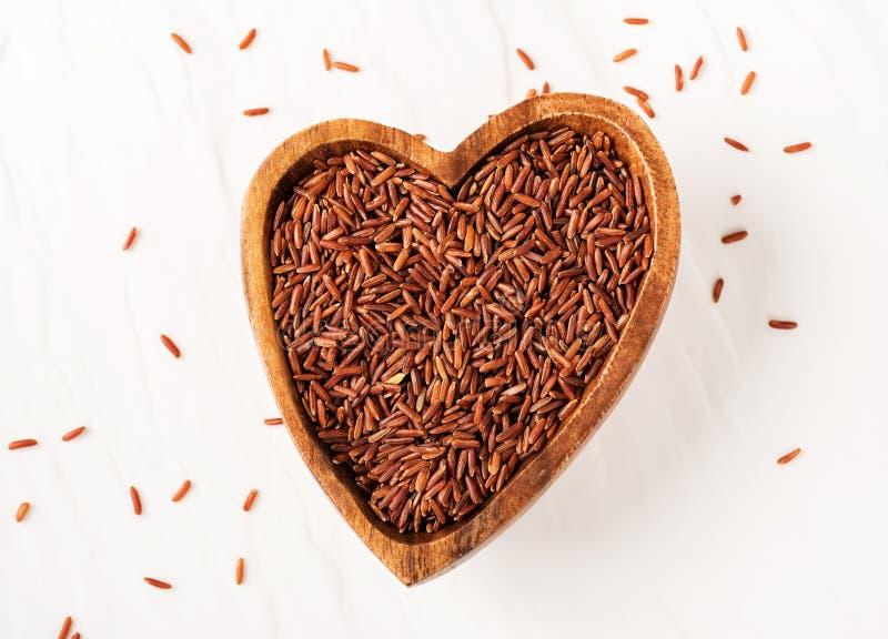 пригорошня сырцового красного риса в деревянном шаре в форме сердца на белой каменной предпосылке стоковое изображение rf