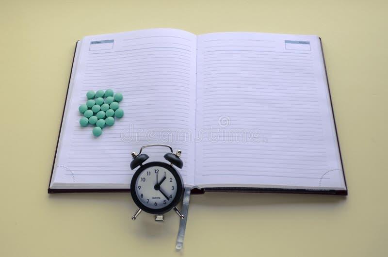 Пригорошня таблеток, таблеток разбросала, таблетки взятия в срок, пишет в календаре и дневнике стоковые фотографии rf
