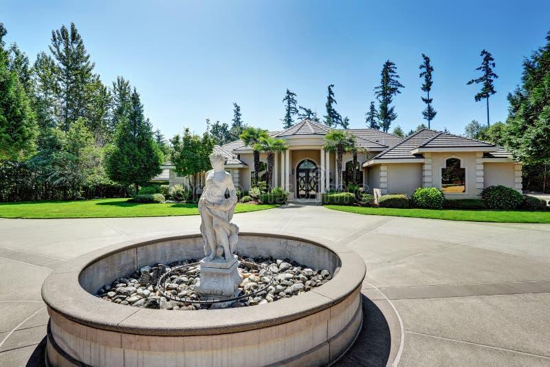 Пригородный роскошный дом с статуей фонтана в дворе перед входом стоковые фотографии rf