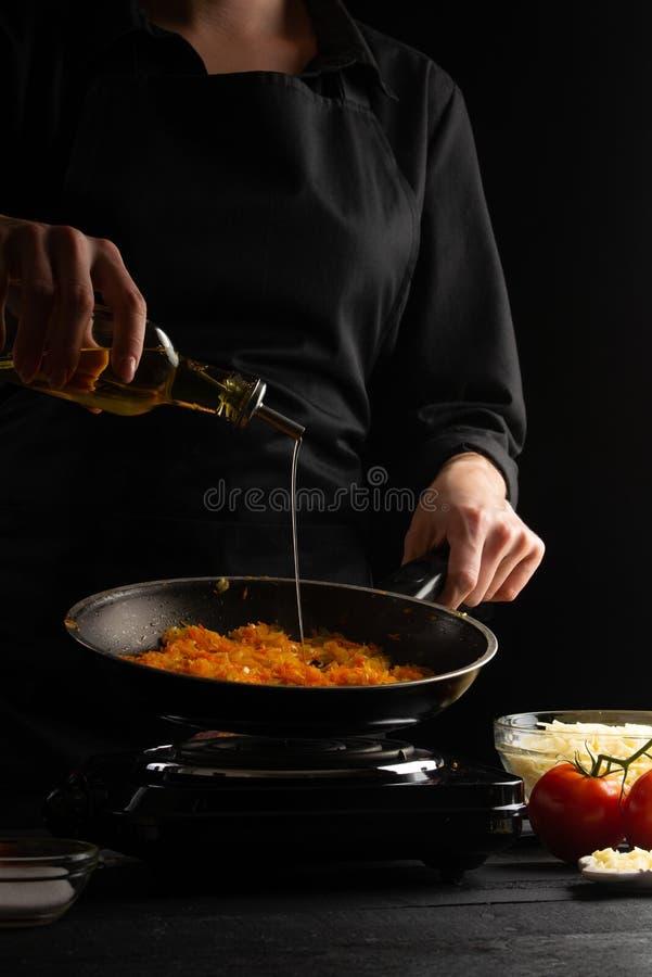 приготовление пищи, лазанья, повар готовят повар, жарят на сковородке оливковое масло Черный фон Итальянско-европейская кухня Вер стоковое фото rf