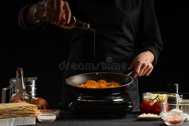 приготовление пищи, лазанья, повар готовят повар, жарят на сковородке оливковое масло Черный фон Итальянско-европейская кухня стоковая фотография rf