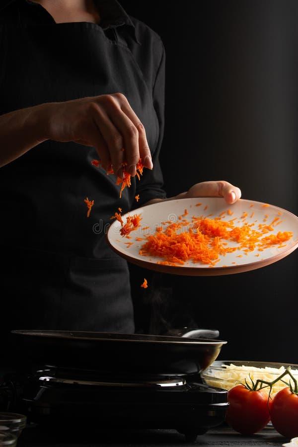 приготовление пищи, лазанья, повар готовят одежду, жарят в сковороде Черный фон Итальянско-европейская кухня Вертикальный выстрел стоковые фотографии rf