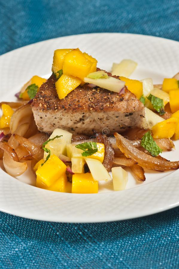 Приготовьте опаленный тунца с caramelized луками и сальсой манго стоковое изображение rf