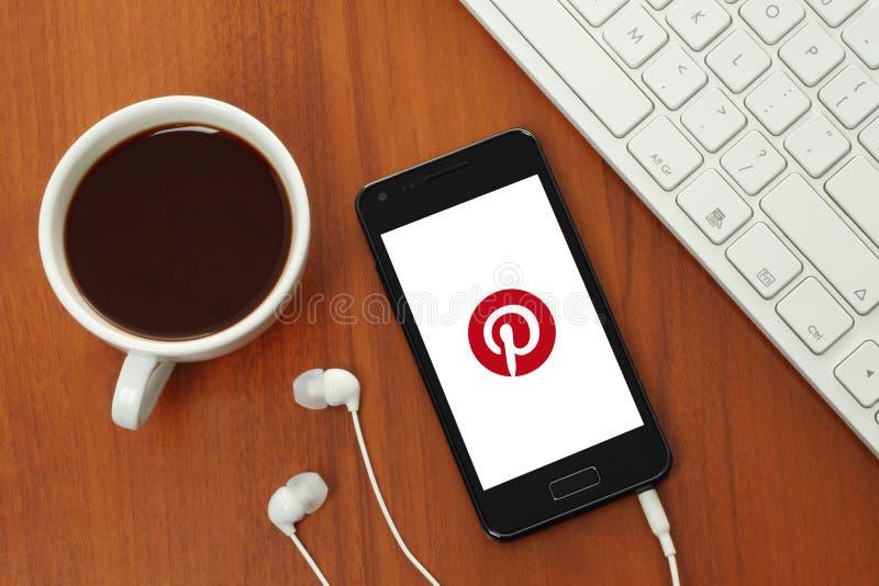 Придайте форму чашки кофе и умный телефон с логотипом Pinterest на своем экране стоковые фотографии rf
