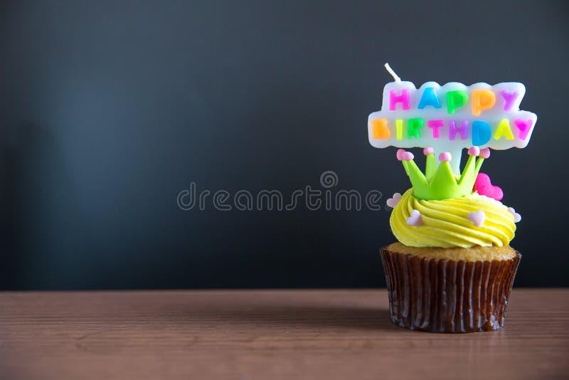 Придайте форму чашки свеча торта и с днем рождения текста на пирожном Пирожное дня рождения с счастливой brithday свечой текста стоковые фото