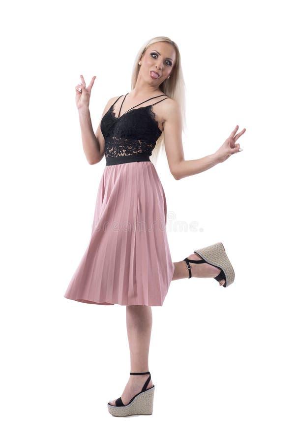 Придурковатая молодая милая белокурая женщина имея потеху вставляя вне язык и показывая знак 2 пальцев стоковое изображение rf