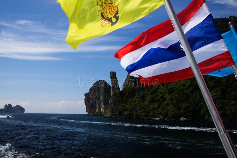 Приезжать на тропический Phi Phi Ko острова с паромом от Пхукета - закройте вверх тайского флага развевая от шлюпки со скалистой  стоковое фото