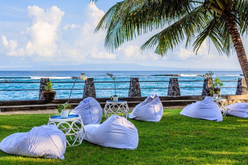 Прием по случаю бракосочетания настроил около океана на заходе солнца - сумок фасоли для гостей и таблиц ротанга стоковые фото
