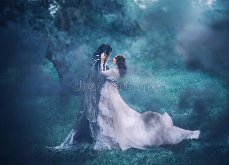 Призрак девушки брюнета и дух еженощного загадочного холодного голубого леса, дамы в белом винтажном платье шнурка с длинным лета стоковые фотографии rf