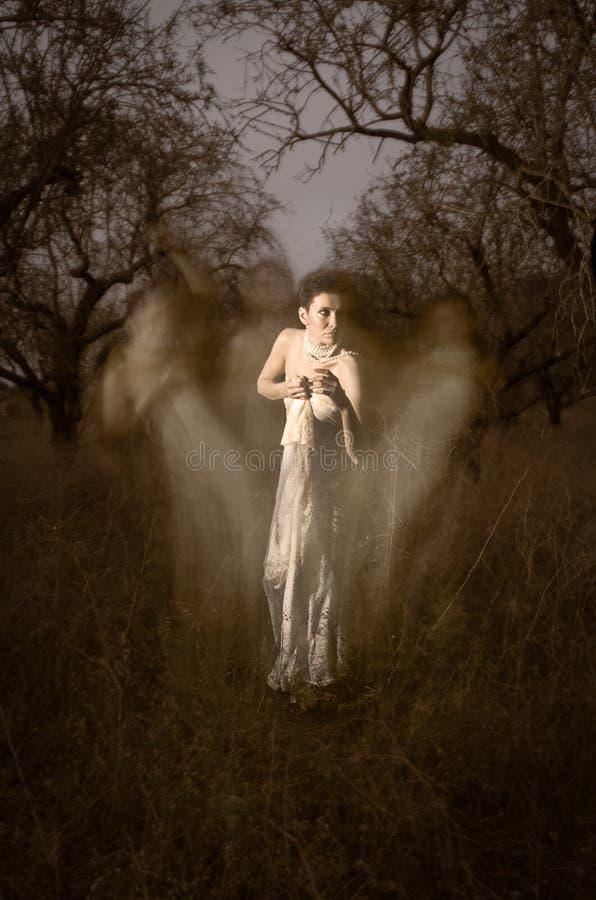 Призрак женщин в белизне окруженный мистическими силуэтами стоковые фотографии rf