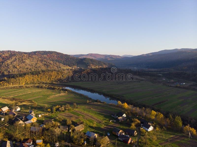 Прикарпатские горы, Украина Воздушный взгляд трутня гор осени с лесами и рекой, лугами и холмами в заходе солнца стоковое изображение rf