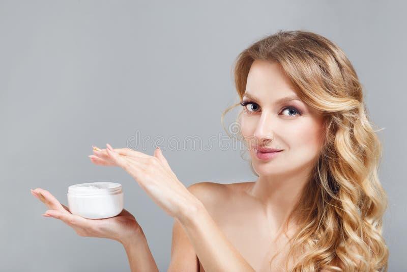прикладывать политуру кожи внимательности прозрачную Красивая девушка blondhair держа опарник с косметической сливк в руках стоковые изображения rf