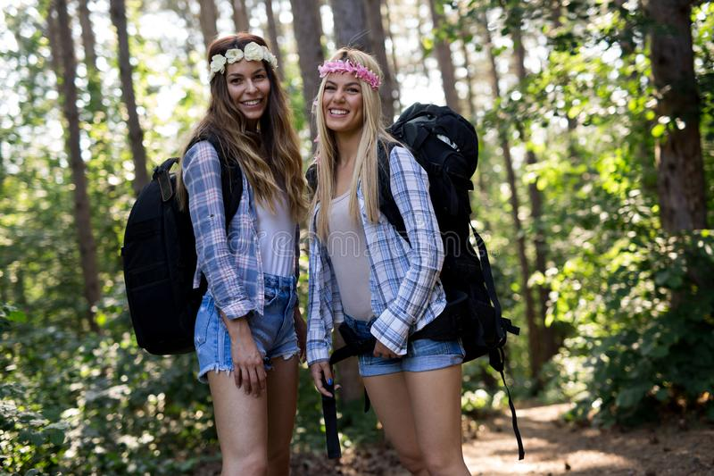 Приключение, перемещение, туризм, поход и концепция людей Счастливые женщины с рюкзаками в лесе стоковые изображения rf
