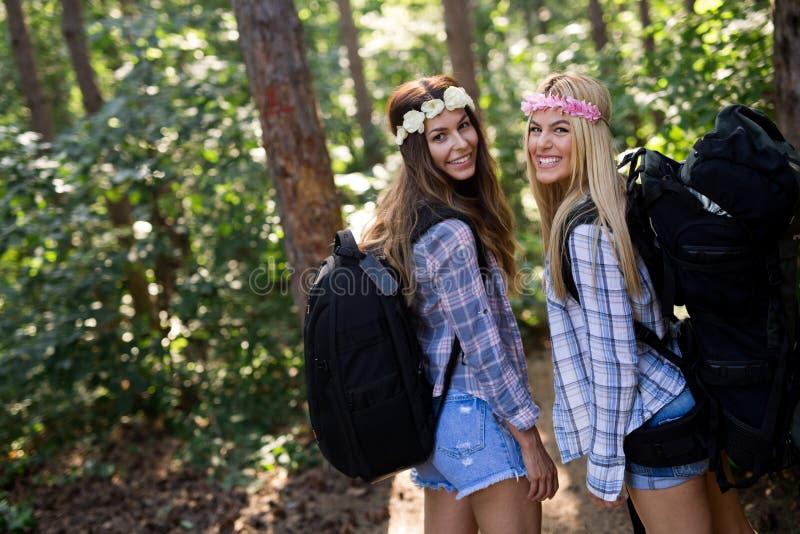 Приключение, перемещение, туризм, поход и концепция людей Счастливые женщины с рюкзаками в лесе стоковое фото