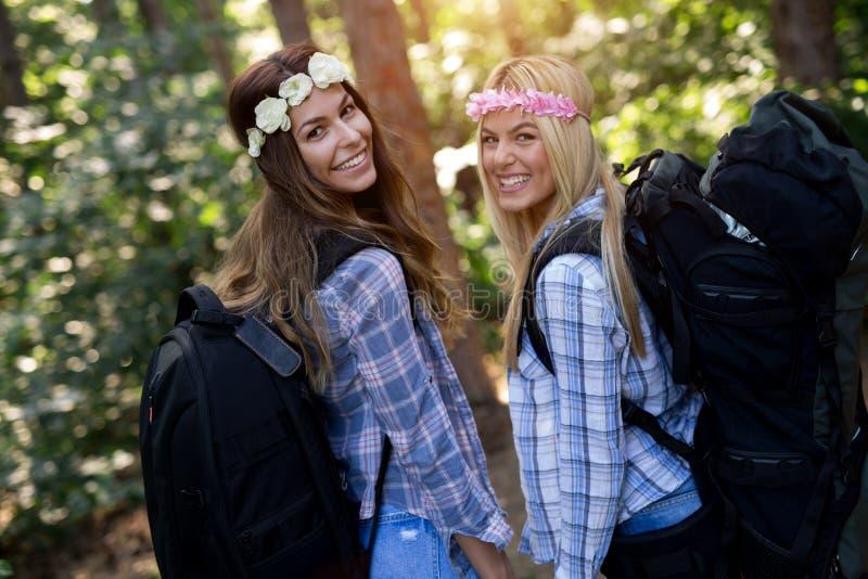 Приключение, перемещение, туризм, поход и концепция людей Счастливые женщины с рюкзаками в лесе стоковые фото