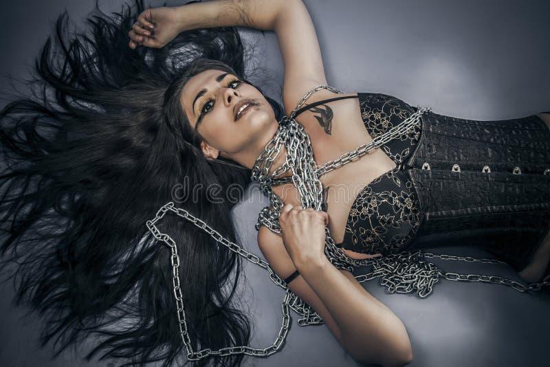 Прикованный, всход моды молодой женщины брюнет в платье фетиша, стоковое изображение rf