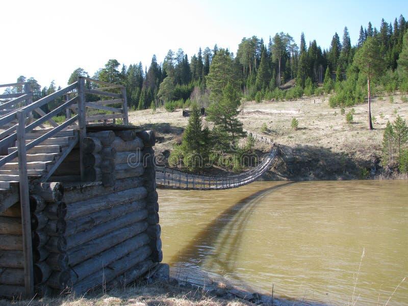 Прикрепленный на петлях деревянный мост над рекой стоковые фотографии rf