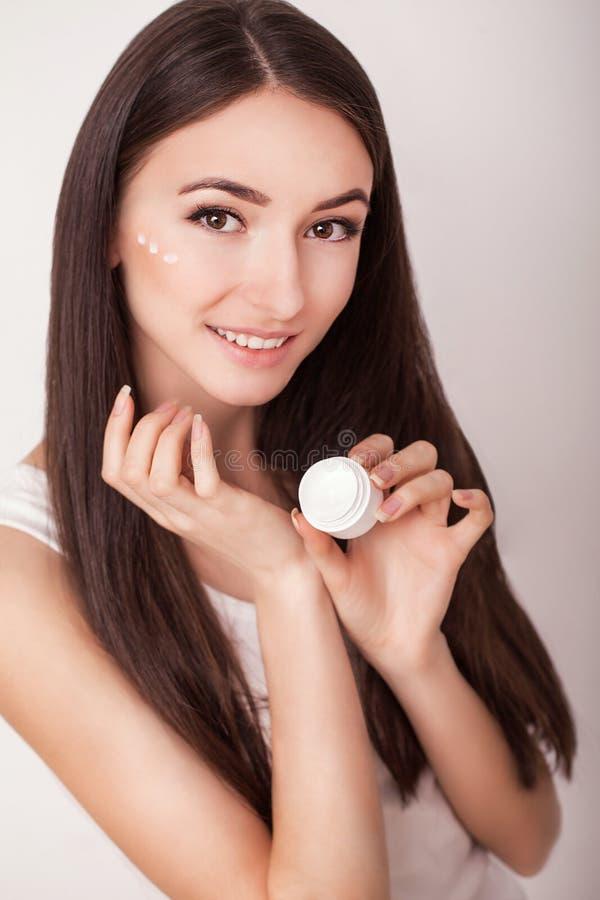 прикладывать политуру кожи внимательности прозрачную Красивая здоровая молодая женщина при длинные волосы, заботя для их кожи Исп стоковое изображение