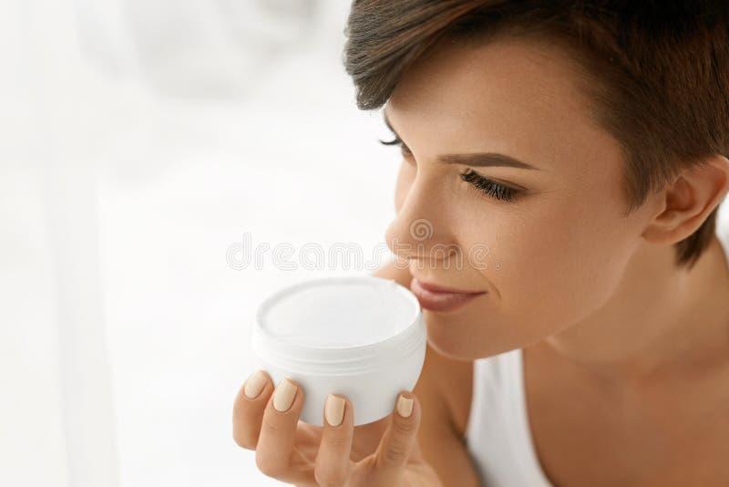 прикладывать политуру кожи внимательности прозрачную Красивая счастливая женщина держа лосьон сливк стороны стоковые изображения rf