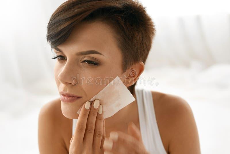 прикладывать политуру кожи внимательности прозрачную Сторона чистки женщины с бумагами масла Absorbing стоковая фотография rf