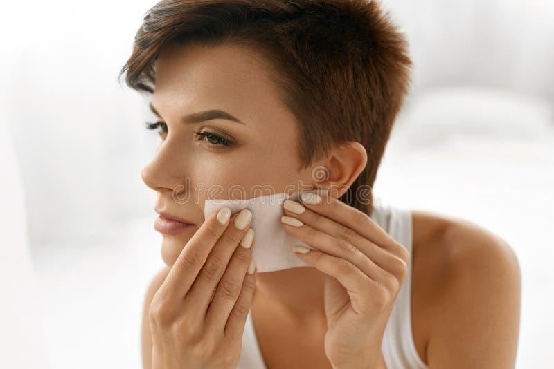 прикладывать политуру кожи внимательности прозрачную Сторона чистки женщины с бумагами масла Absorbing стоковые фото