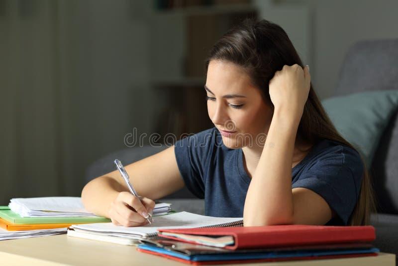 Прилежный студент уча принимающ примечания в ноче стоковые фото