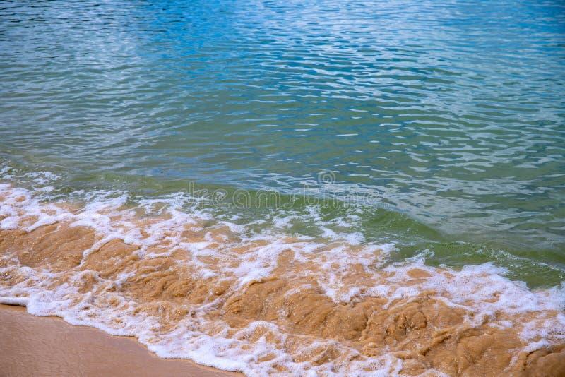 Прилив морской воды над желтым пляжем песка Тропическое фото концепции взморья Пенообразная волна моря на пляже песка стоковая фотография