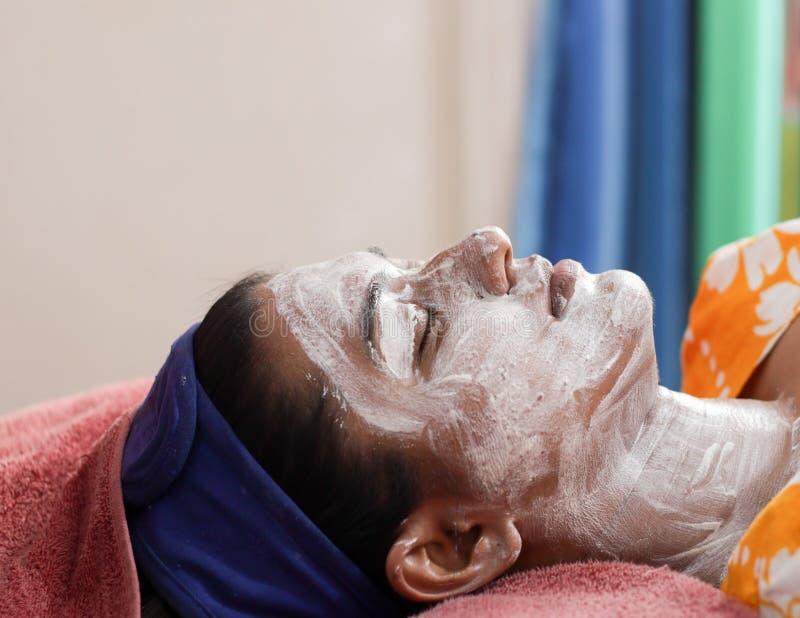 Приложение лицевой сливк маски пакета на стороне дамы с диапазоном волос с глазами закрыло Взгляд со стороны стоковая фотография