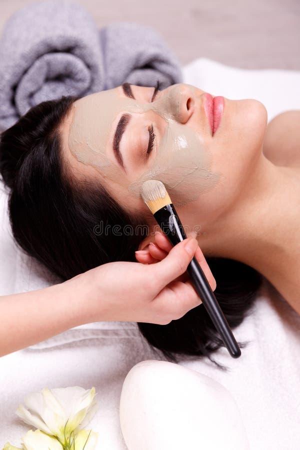Применение маски курорта лицевое Красивая расслабленная женщина имея лицевой щиток гермошлема глины в курорте стоковое изображение