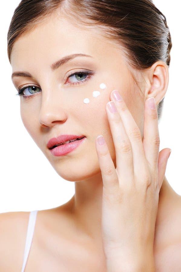 применяться вокруг косметической сливк eyes женская кожа стоковые изображения