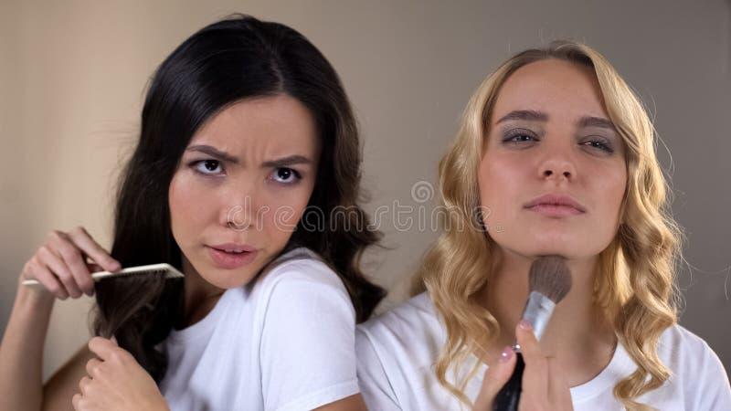 Применяться 2 девушек составляет, воюющ для места перед зеркалом, соперничество, завистливость стоковое изображение
