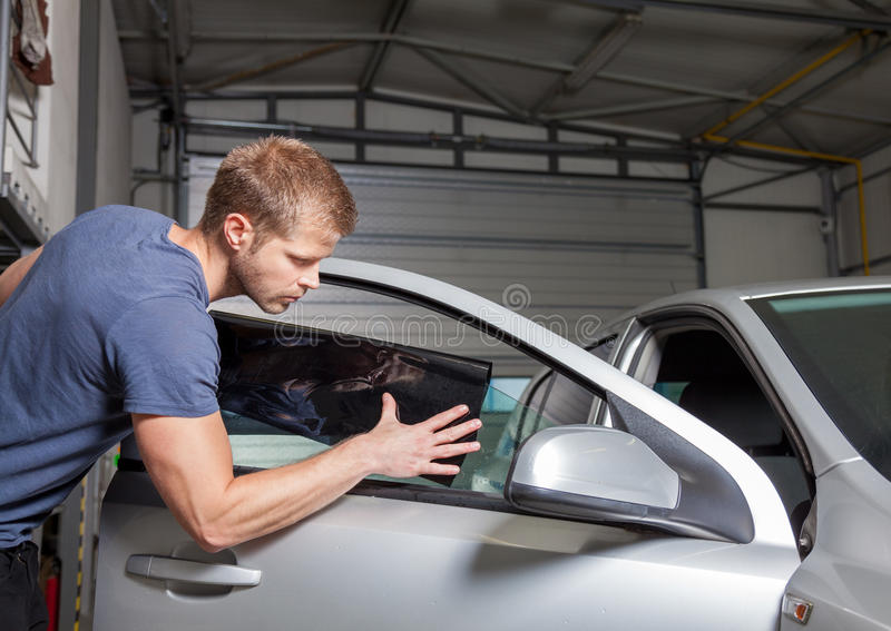 Применяться подкрашивающ фольгу на окно автомобиля стоковые изображения