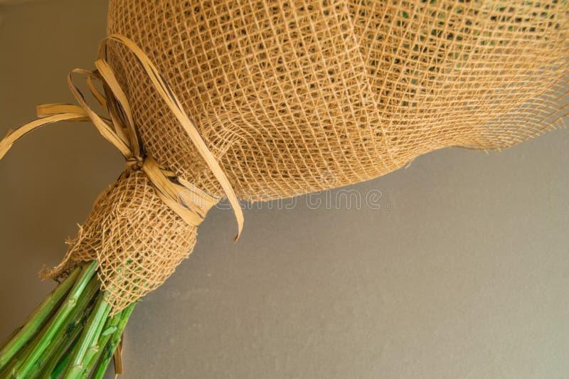 Пример упаковки букета цветов в коричневой цветочной сетке, расположенной на сером фоне стоковые фото