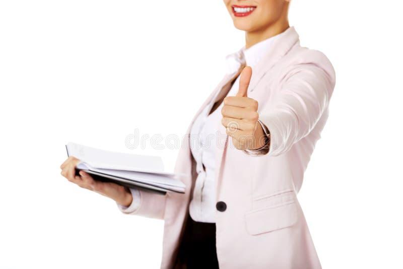 Примечания и выставка удерживания бизнес-леди улыбки открытые thumb вверх стоковые фотографии rf