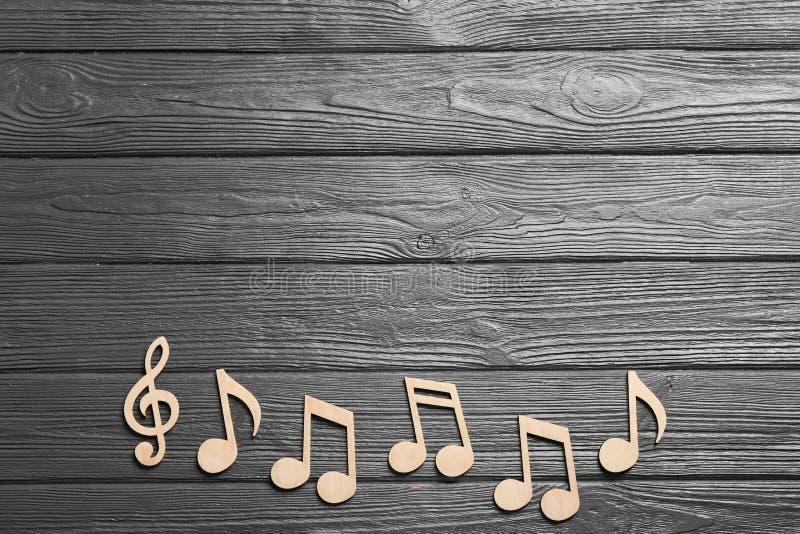 Примечания музыки и дискантовый ключ на деревянной предпосылке, взгляде сверху стоковая фотография