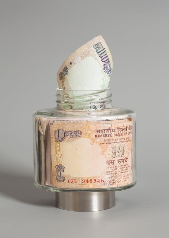 Примечания рупии валюты денег индийские в стеклянном опарнике стоковое изображение