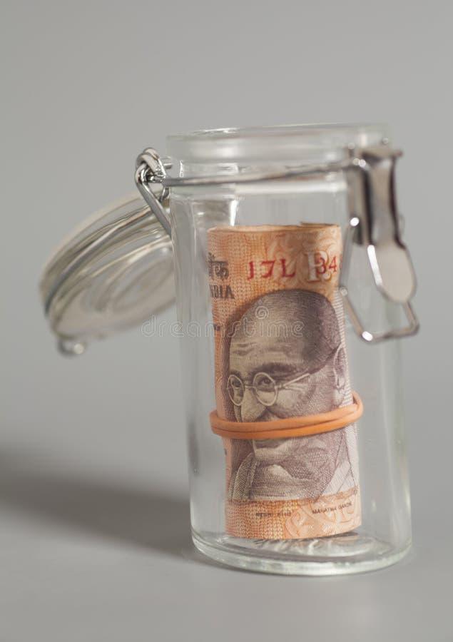 Примечания рупии валюты денег индийские в стеклянном опарнике стоковая фотография rf