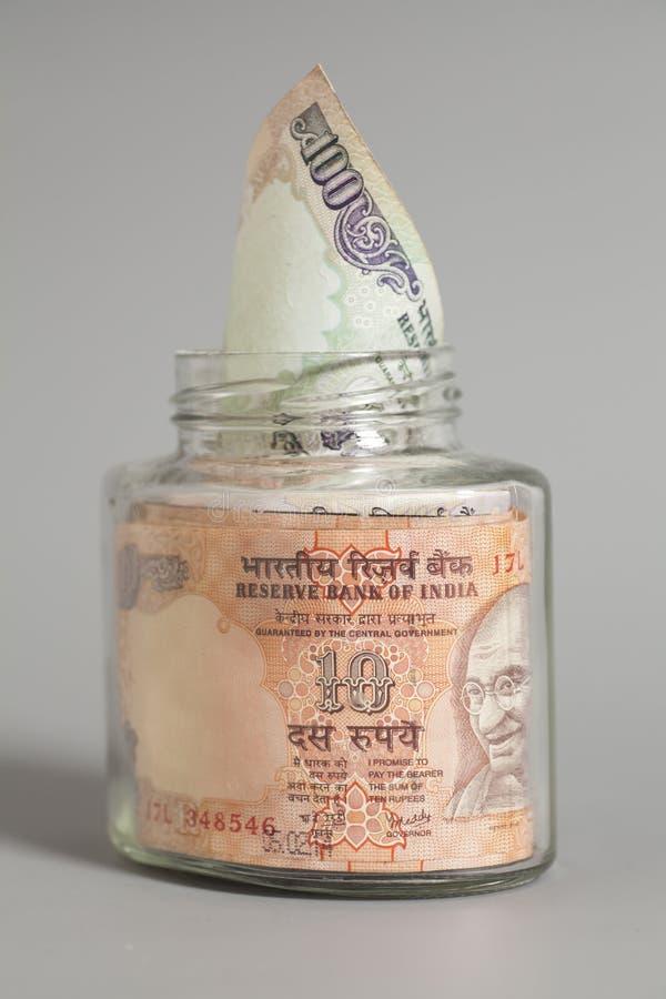 Примечания рупии валюты денег индийские в стеклянном опарнике стоковая фотография