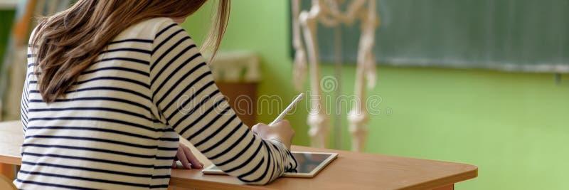 Примечания сочинительства студентки используя цифровой планшет в уроке биологии Концепция образования поколения z стоковая фотография
